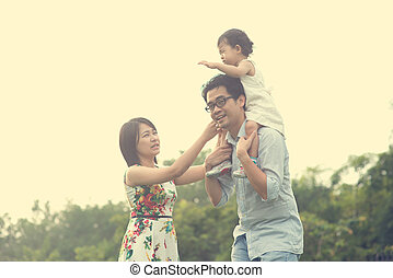 asian family playing and enjoying quality time outdoor