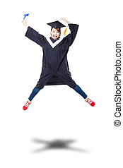 Happy female student in graduate robe jumping against white...