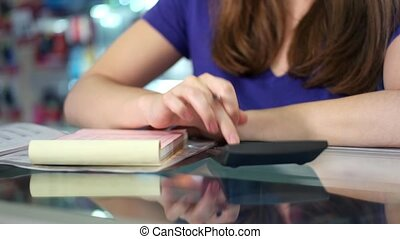 Woman Checking Bills And Invoices - Young white female...