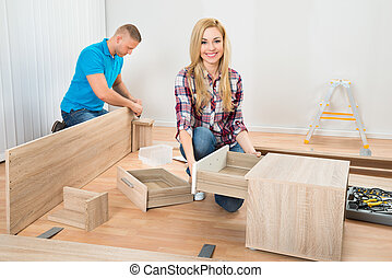Couple Assembling Wooden Furniture - Portrait Of Young...