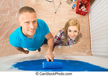 Young Couple Painting In New Home