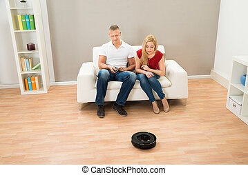 Couple With Remote Control And Robotic Vacuum Cleaner -...