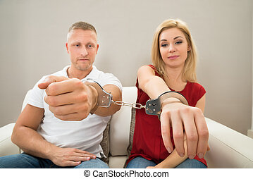 Couple Handcuffed Together - Portrait Of Unhappy Young...