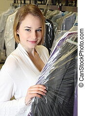 Woman picks up clothes in a  Dry Cleaning