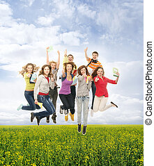 Group of smiling teenagers jumping together and looking at...