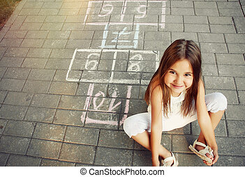 beautiful cheerful little girl playing hopscotch on...