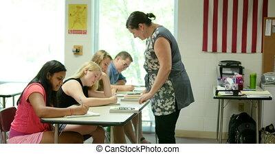 Teacher helping students with their - High school teacher...