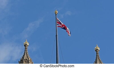 England flag waving on the top of Westminster Abbey With the...