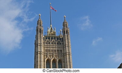 Tall tower of the Westminster Abbey with the flag on top on...