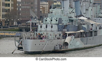 The white warship displayed on Thames river. People go...