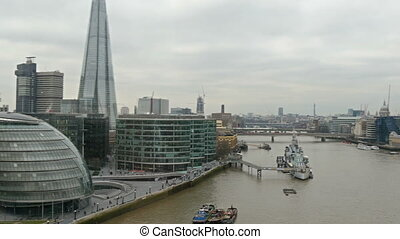 Tall buildings alongside the Thames river. Shown also are...