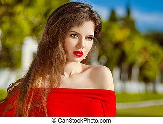 Outdoor portrait of fashion brunette model in red dress...