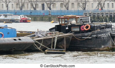 Big boats docking on the Thames river with cargos inside...