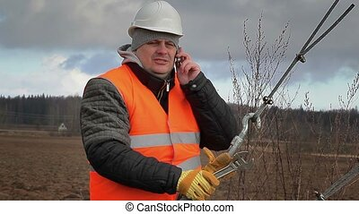 Worker with cell phone and adjustable wrench on field