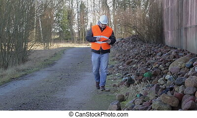 Worker with tablet PC on road near at piles of stones