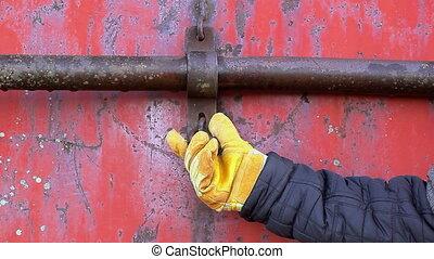 Man try open padlock on red metal door