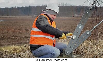 Worker with adjustable wrench near tensioner on field