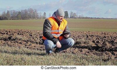 Farmer with tablet PC near plowed field