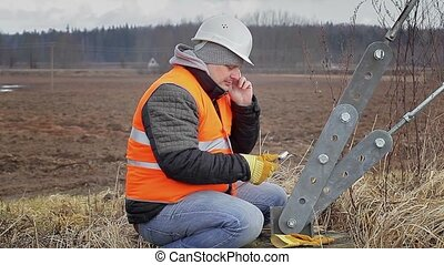 Worker with cell phone and adjustable wrench near tensioner