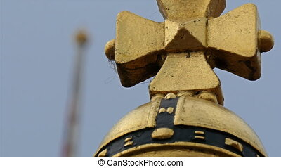 A small golden cross on the tip of a pole It is a symbol of...