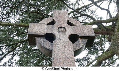 A circle with a cross tombstone in a cemetery It is one of...