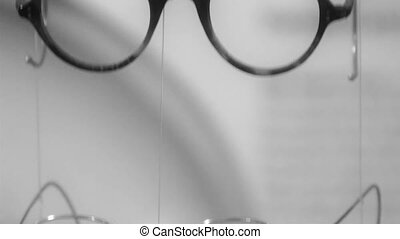 Four eyeglasses hanging on a string They are black framed...