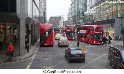 The busy morning street in London with the buses and the...
