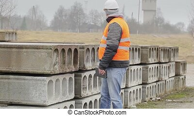 Civil engineer working with tablet PC near construction...