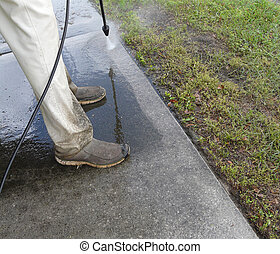 Male Pressure Washing Sidewalk - Male do-it-yourselfer...