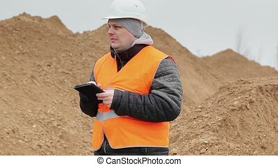 Civil engineer working with tablet PC at a pile of sand