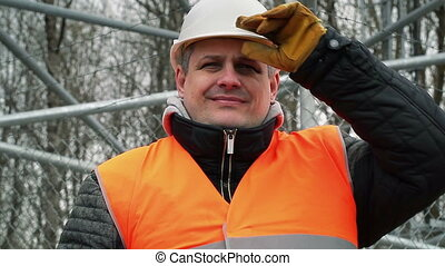 Happy worker with adjustable wrench at outdoors