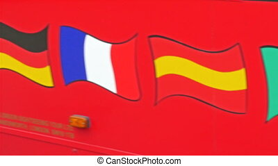 Different kinds of flags drawn on the side of the red bus