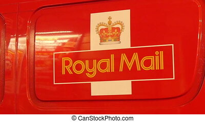 A modern royal mail carrier in London. It is a red van that...