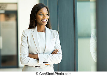 young african businesswoman looking out the window - happy...