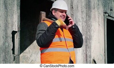Worker with cell phone and sledge hammer near the wall