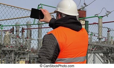 Electrical engineer filmed with tablet PC at power plant