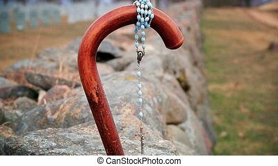 Walking stick with rosary near stone fences