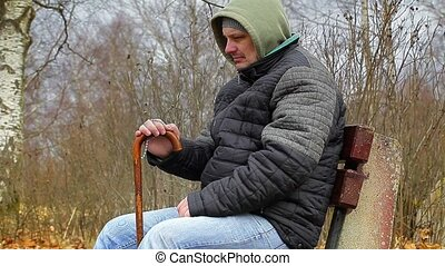 Man with rosary and walking stick on bench