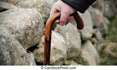Mans hand with walking stick and a rosary