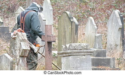 A man in uniform mowering the tall grass in the cemetery To...