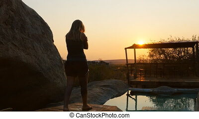 lonely woman enjoys sunset - woman relaxing looking the...