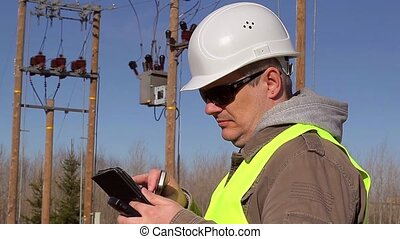 Electrical engineer with tabled PC and cell phone at...