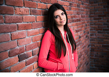 Portrait of attractive woman leaning on the brick wall and...