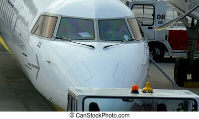Two workers on a airport jeep infront of an airplane. There...