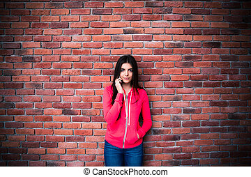 Beautiful woman talking on the phone over brick wall....