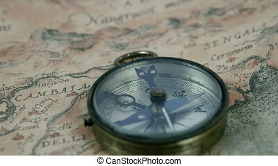 A round compass with its pointer moving pointing to some...