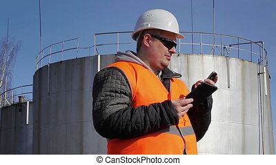 Engineer with cell phone and tablet PC near oil tank