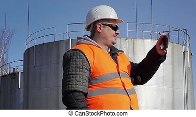 Engineer filmed with tablet PC near oil tank