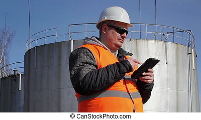 Engineer working with tablet PC near oil tank