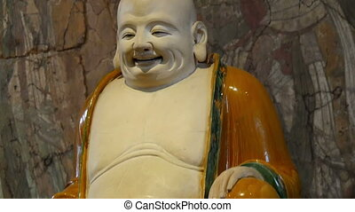 A buddha like statue of a bald man wearing orange suit and...
